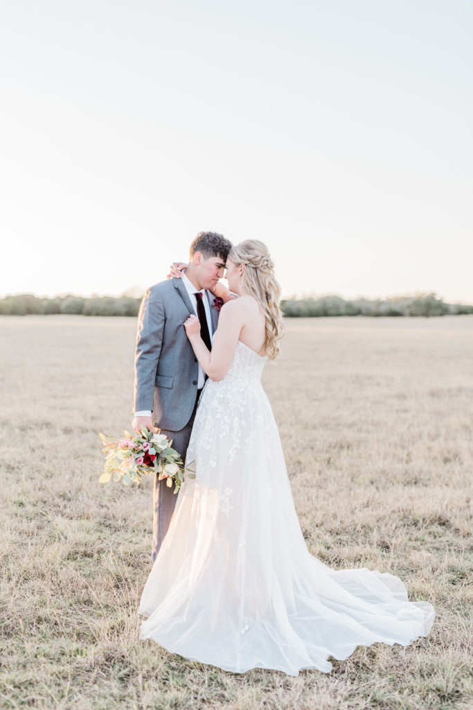 Bride and Groom Sunset Portrait Strapless Dress Grey Suit Velvet Tie Blush and Wine Bouquet Eucalyptus   Wagon Springs Ranch in Burnet TX by DFW Dallas Fort Worth wedding photographer Karina Danielle Photography